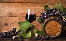 Una copa de vino, barrica, uvas.