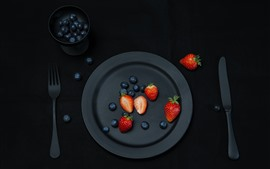Black plate, strawberry, blueberry, fork, knife