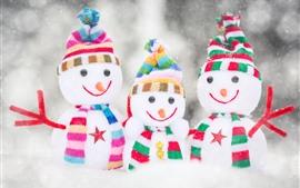 Tres muñecos de nieve, nieve, juguetes.