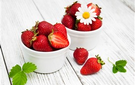 Two cups of fresh strawberries, white flower