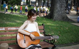 幸せな少女は、ギター、ベンチ、公園を再生します