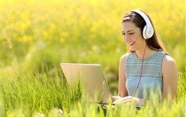 Preview wallpaper Happy girl use notebook, headphone, grass, summer