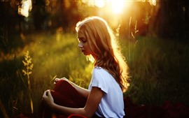Preview wallpaper Blonde girl, sit, grass, sunshine, glare, summer
