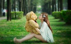 Cabelo comprido Menina asiática, pelúcia, urso de brinquedo, grama, beijo