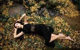 Preview wallpaper Black skirt girl, lying on ground, foliage