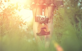 Preview wallpaper Girl, legs, camera, grass, hazy, sunshine