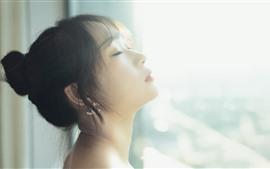 Vorschau des Hintergrundbilder Mädchen, das den Sonnenschein, das Fenster, den dunstigen, grellen Glanz glaubt