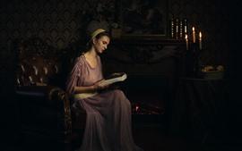 Garota de estilo retrô, leia o livro, lareira, velas, livros