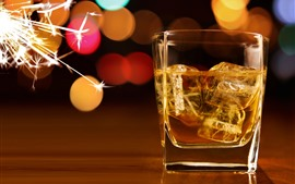 Ice cubes, whiskey, glass cup, sparks