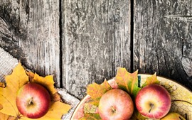 Some apples, maple leaves, wood board