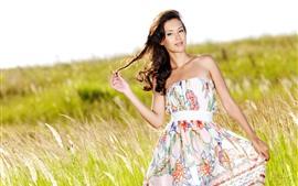 Chica de pelo negro en verano, falda, hierba
