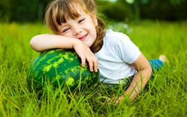 Lovely little girl and watermelon, grass, meadow