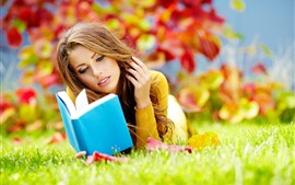 Brown hair girl, reading book, grass