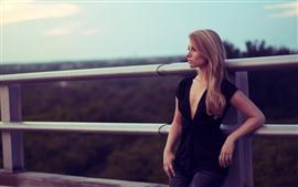 Fille blonde, clôture métallique