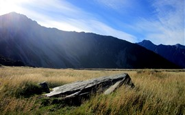 Preview wallpaper New Zealand, grass, rock, mountains, sun rays, blue sky