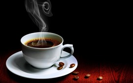Una taza de café, vapor, granos de café, fondo negro