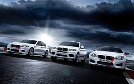 Vista frontal de tres coches BMW blancos