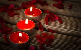 Três velas vermelhas, chama, pétalas