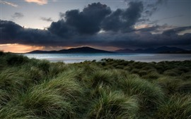 Preview wallpaper Mountains, sea, beach, grass, clouds, dusk