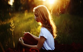 Blonde girl sit on grass, sunshine, backlight