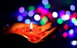 Hands, candle, flame, colorful light circles