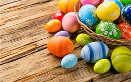 Some colorful Easter eggs, basket, wood table