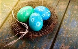 Three blue Easter eggs, nest