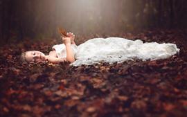 Linda niña duerme en el suelo, falda blanca, hojas