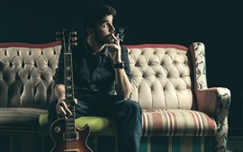 Man, cigarette, guitar, sofa
