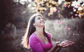 Garota feliz, sorriso, olha para pétalas de rosa