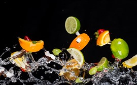 Un poco de rebanada de frutas, naranja, limón, salpicaduras de agua, fondo negro