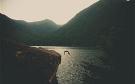 Озеро, горы, человек прыгают к воде
