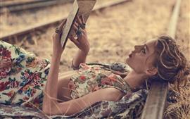 Девушка читает книгу, лежа на земле, железная дорога