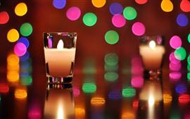 Copa de vidrio, vela, llama, círculos ligeros coloridos
