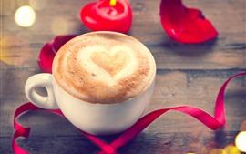 Um xícara de café, coração de amor, espuma, fita vermelha